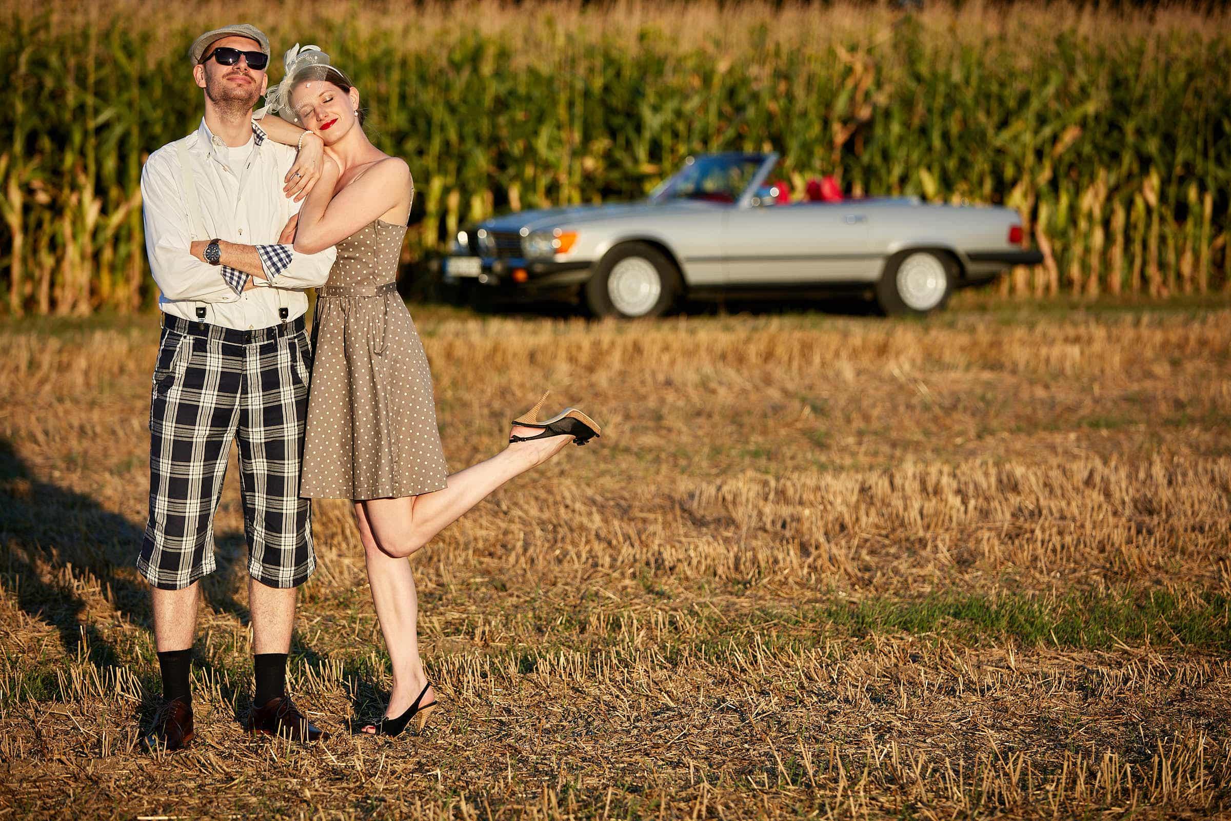 After-Wedding-Shooting in Industrieromantik und Brautkleid Ein Hochzeitspaar steht verträumt auf einem Getreidefeld und schaut in die untergehende Sonne.
