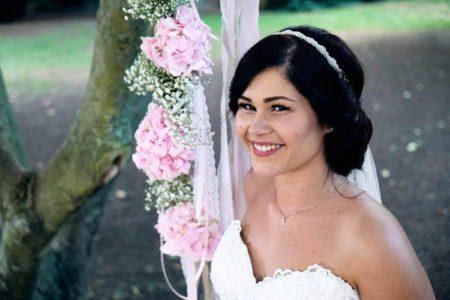 Hochzeit im Ketschauer Hof Eine traumhaft schöne Braut sitzt im Garten des Ketschauer Hofs in Deidesheim, auf einer Blumenschaukel.