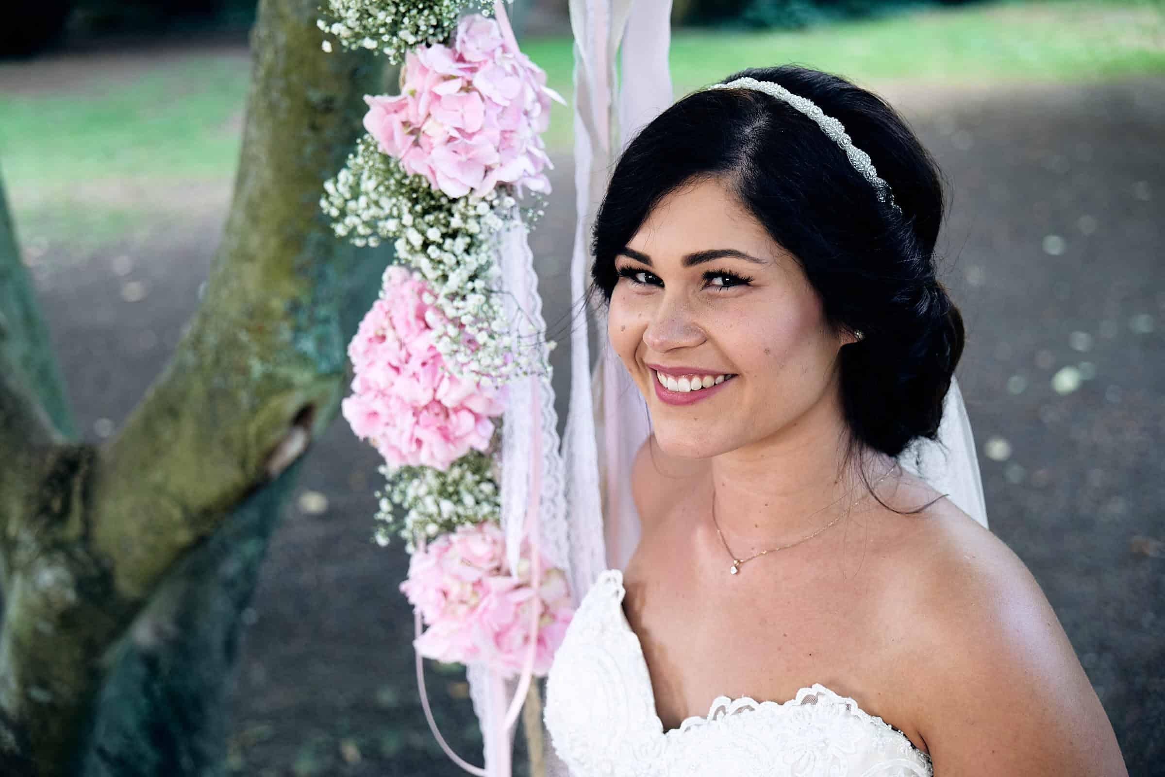 Hochzeit im Ketschauer Hof-Eine traumhaft schöne Braut sitzt im Garten des Ketschauer Hofs in Deidesheim, auf einer Blumenschaukel.