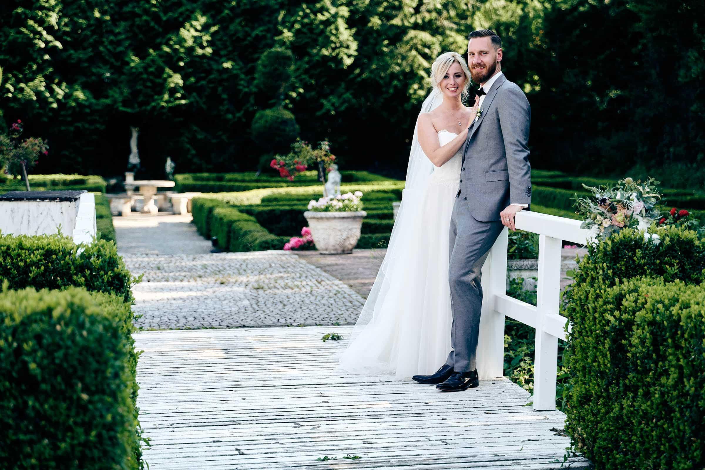 Hochzeitsreportage in der Haldmühle Ein frisch verheiratetes Paar posiert auf einer Brücke beim Brautpaarshooting in der Haldmühle Bissersheim