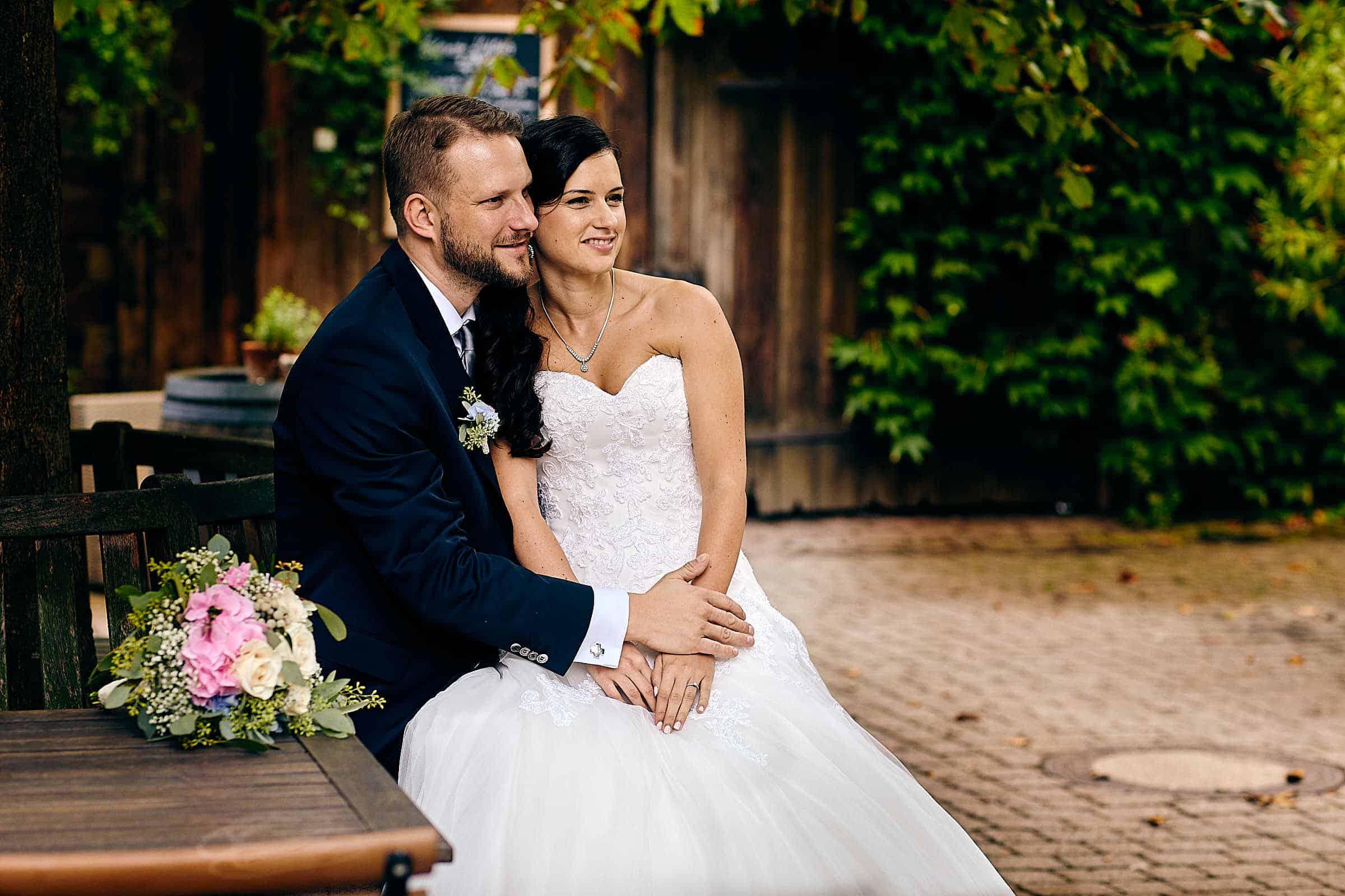 Hochzeitsreportage im Hotel Grenzhof Heidelberg-Das Brautpaar sitzt im Garten und wird vom Hochzeitsfotografen Onelovephoto fotografiert