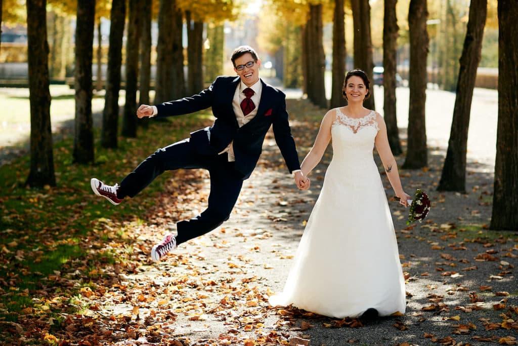 Der Bräutigam macht ein Freudensprung beim Shooting im Schlossgarten Schwetzingen
