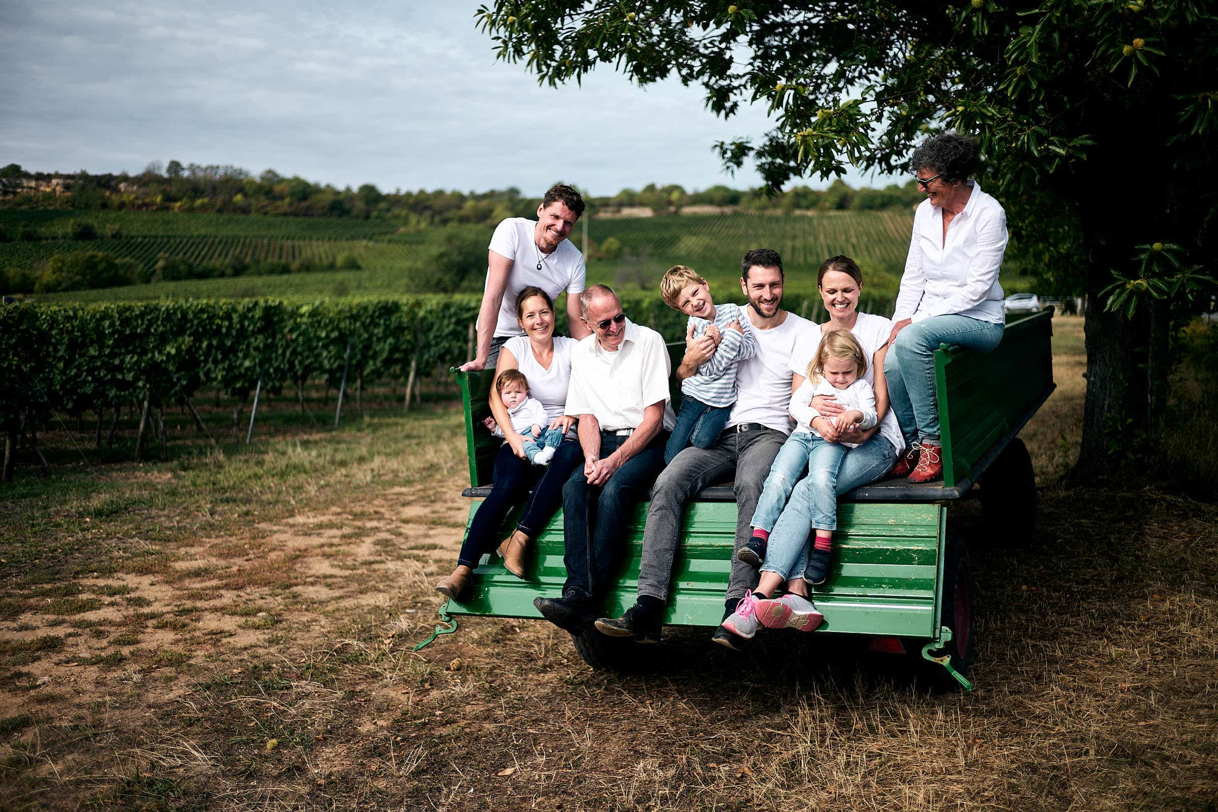 familien shooting mit drei generationen - Eine Familie sitzt für das Shooting auf einen Anhänger eines Wein-Bauern in der Pfalz.