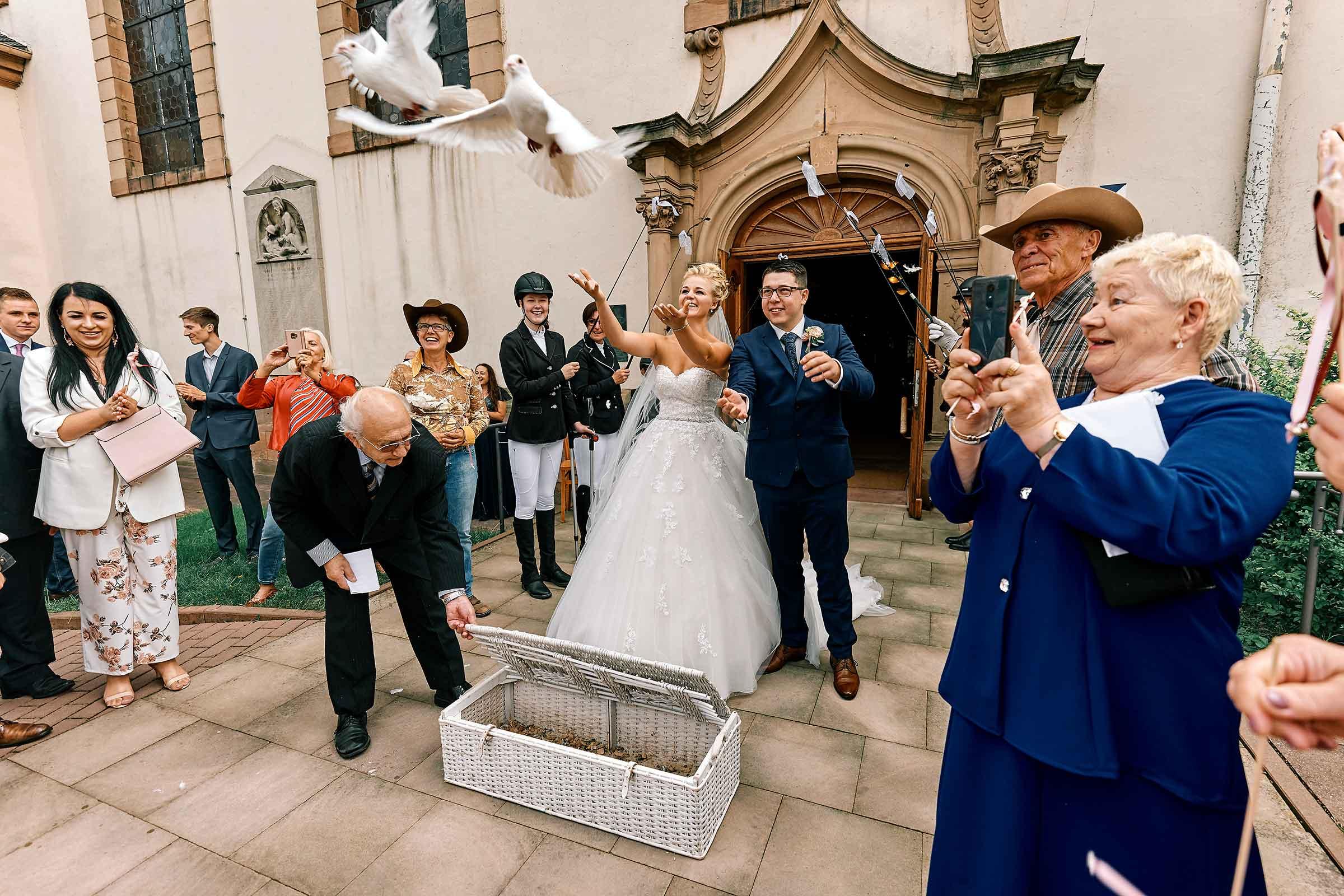 Eine Deutsch-Polnische Hochzeit in der Pfalz-Das Brautpaar lässt Tauben fliegen nach ihrer Trauung.