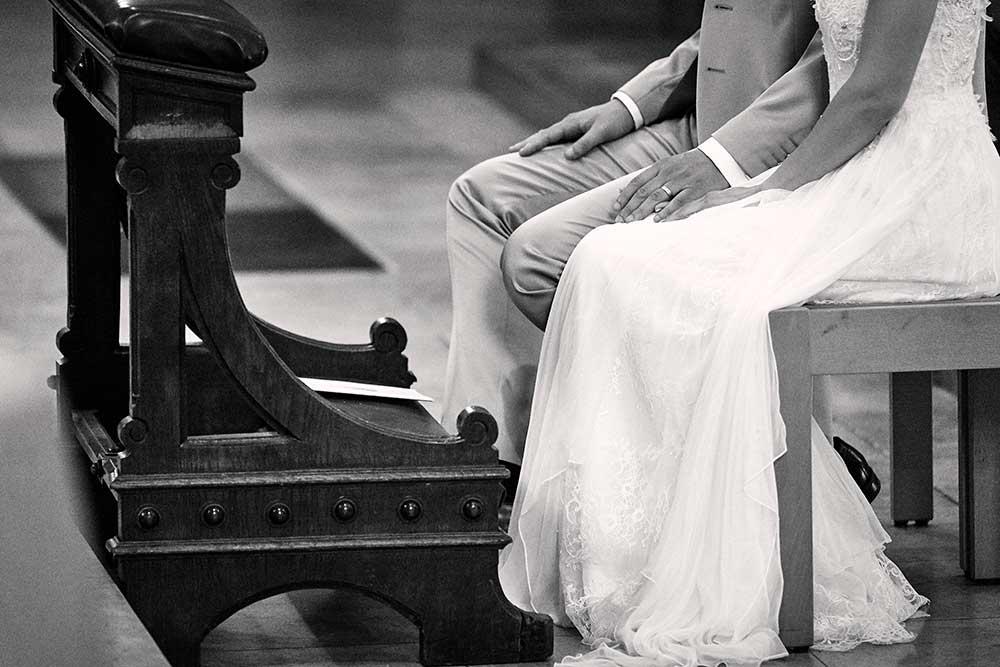 UNVERBINDLICHE BUCHUNGSANFRAGE-Ein Hochzeitspaar sitzt vor dem Trau-Altar und hält sich die Hände