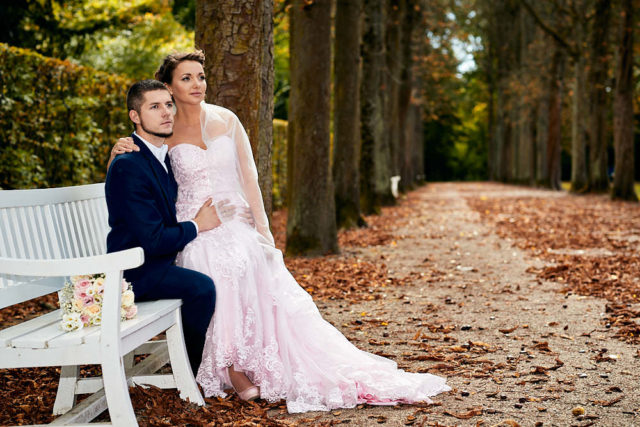 Pre- und After-Wedding-Shooting- Eine wunderschöne Braut sitzt auf dem Oberschenkel des Bräutigams