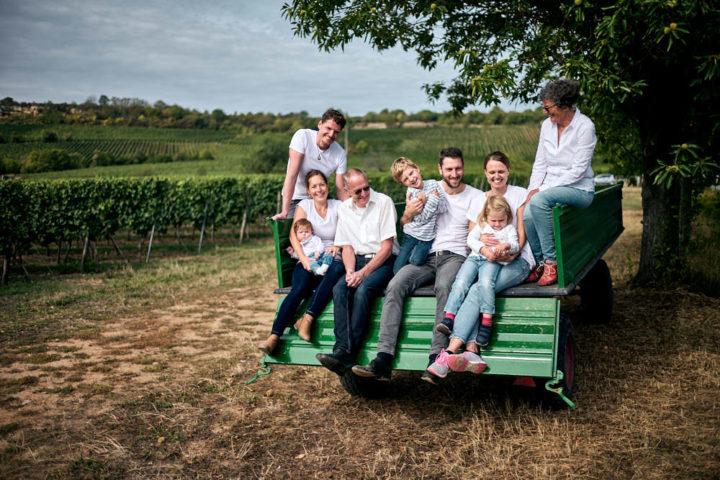 FAMILIEN-SHOOTING-Eine Familie mit Kindern, Eltern und Großeltern sitzen auf einen Anhänger eines Wein-Bauern in der Pfalz