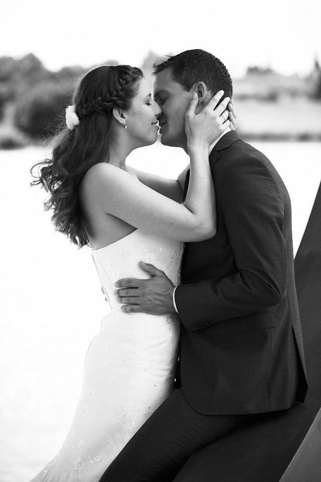 Ein Hochzeitspaar küsst sich am Neckar in Ladenburg.