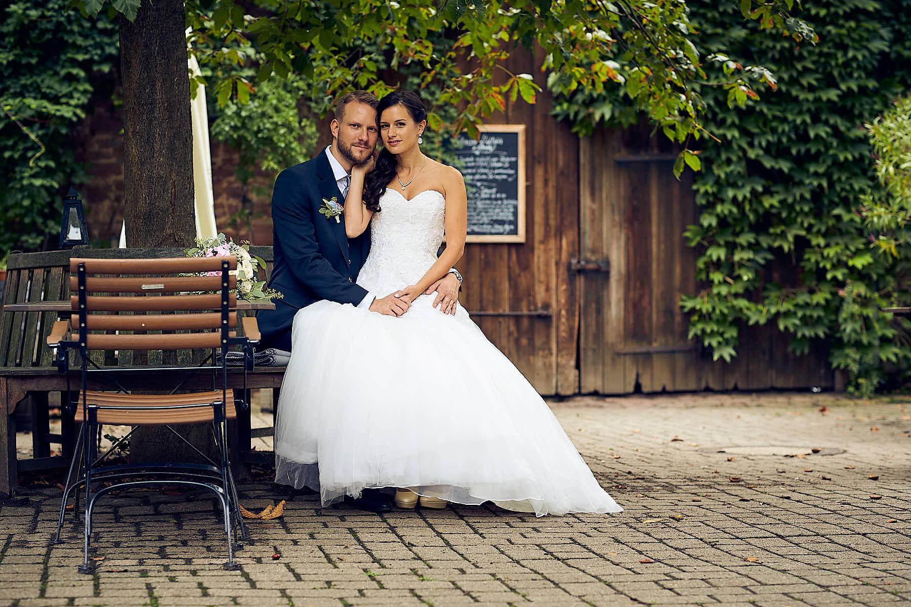 Hochzeitsfotografie Mannheim Heidelberg-Ein Hochzeitspaar sitzt im Garten des Hotel Grenzhof und lässt sich für ein Shooting fotografieren.