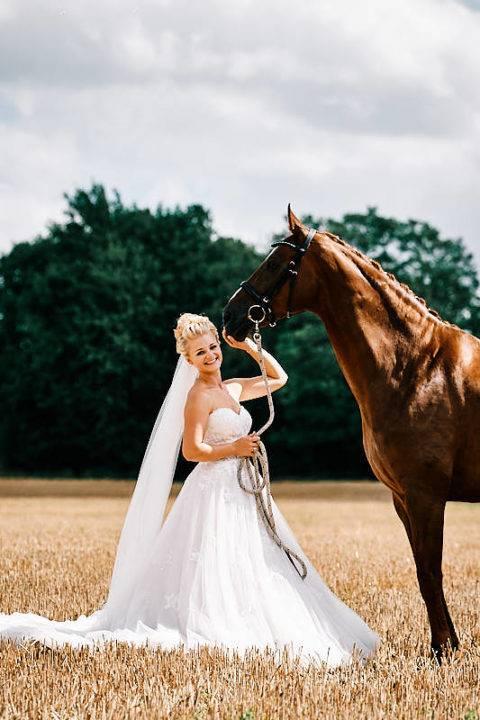 After Wedding Shooting-Eine Braut steht mit ihren Pferd auf einen Getreidefeld.