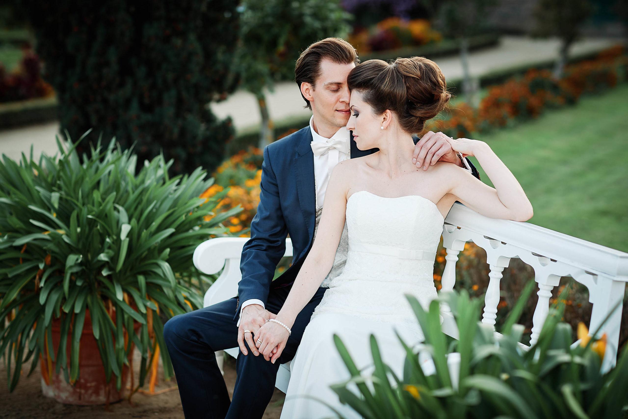 Hochzeitsfotograf in Darmstadt Ein verliebtes Hochzeitspaar sich auf einer weissen Parkbank im Herrngarten in Darmstadt