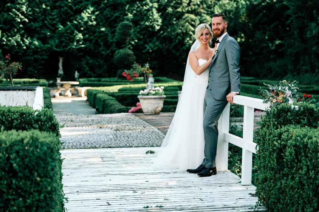 Ein frisch verheiratetes Paar posiert auf einer Brücke beim Brautpaarshooting in der Haldmühle Bissersheim