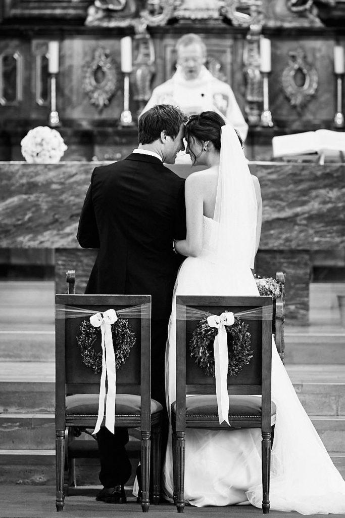 Ein Hochzeitspaar schaut sich tief in die Augen bei der kirchlichen Trauung vor dem Altar