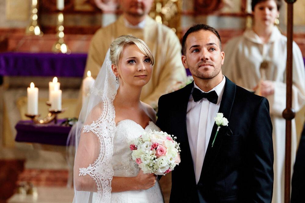 Braut und Bräutigam schauen gerührt zu der Sängerin ihrer kirchlichen Hochzeit in Ludwigshafen.