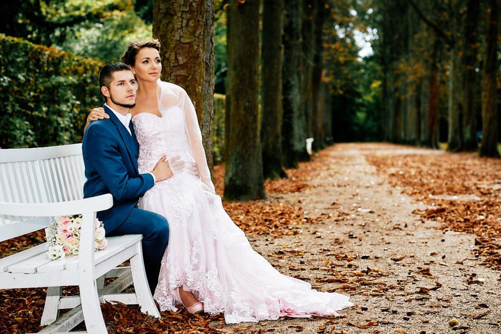 Ein wunderschönes Hochzeitspaar sitzt auf einer weißen Parkbank, beim After-Wedding-Shooting im Schlossgarten Schwetzingen.