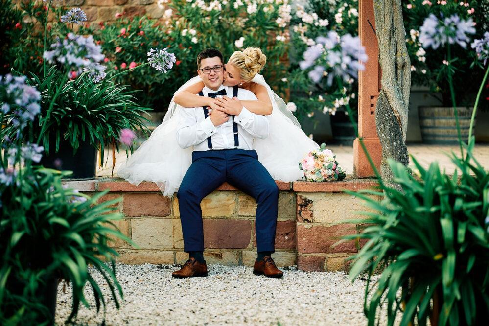 Die Braut küsst ihren Bräutigam zärtlich von hinten auf den Hals. After-Wedding-Shooting in der Pfalz