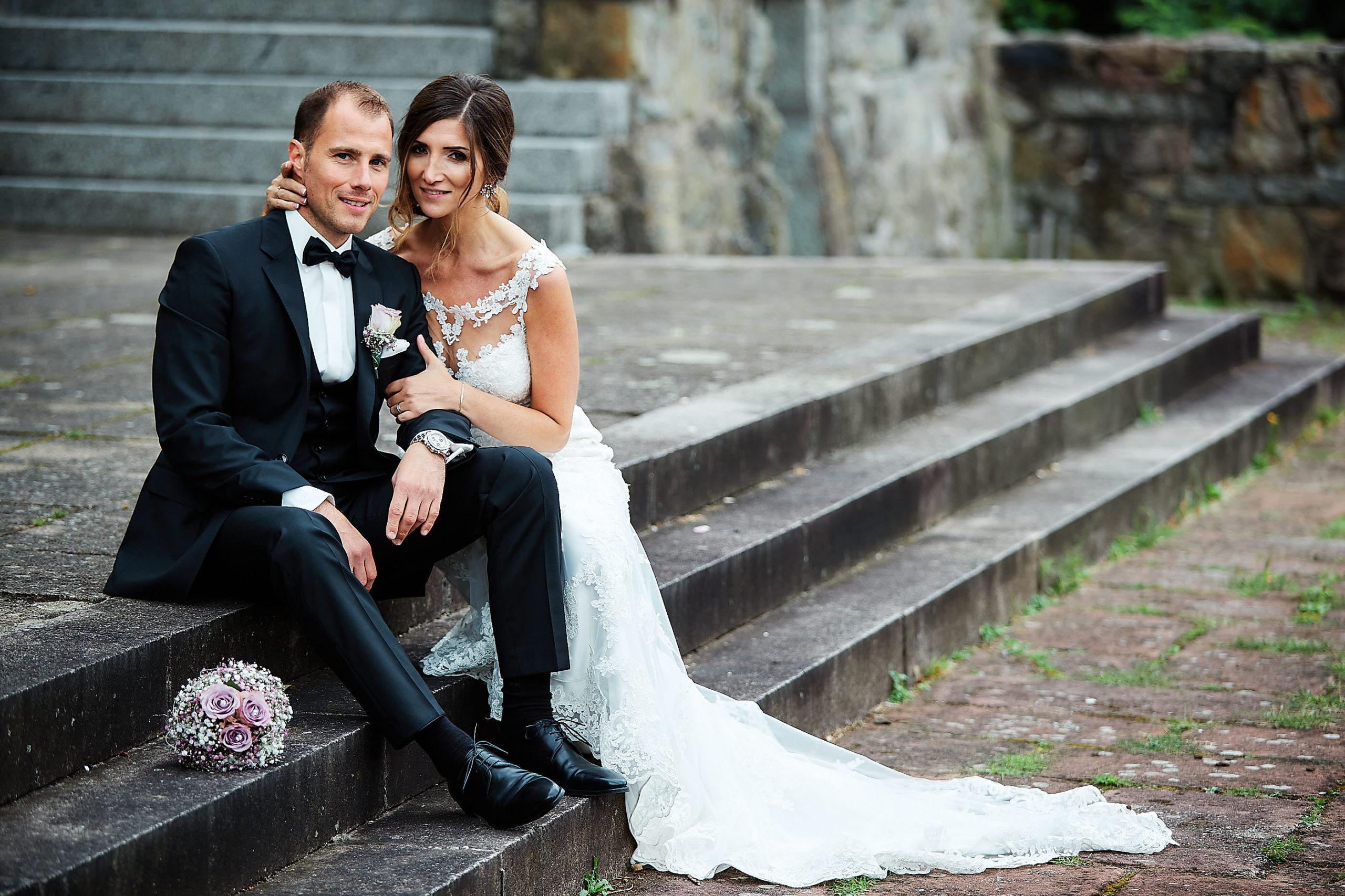 Ein wunderschönes Hochzeitspaar sitzt auf einer Treppe auf der Wachenburg in Weinheim