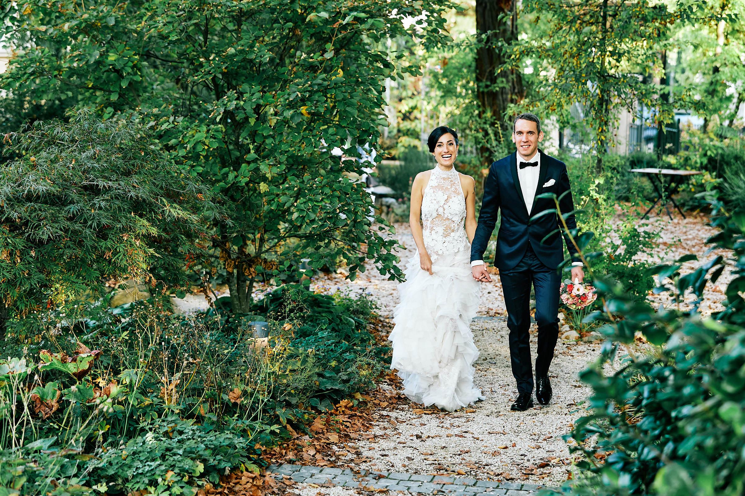 Hochzeit bei Von Winning-Das Hochzeitspaar läuft durch den Garten Hand in Hand - Als Hochzeitsfotograf bei Von Winning in Deidesheim