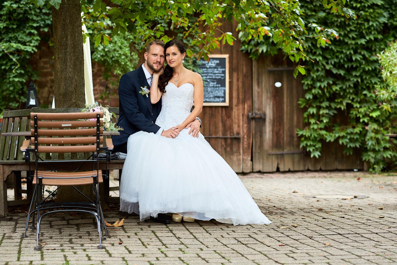 Hochzeitsreportage im Hotel Grenzhof Heidelberg - Die Braut sitzt auf dem Oberschenkel des Bräutigams und beide schauen in die Kamera.