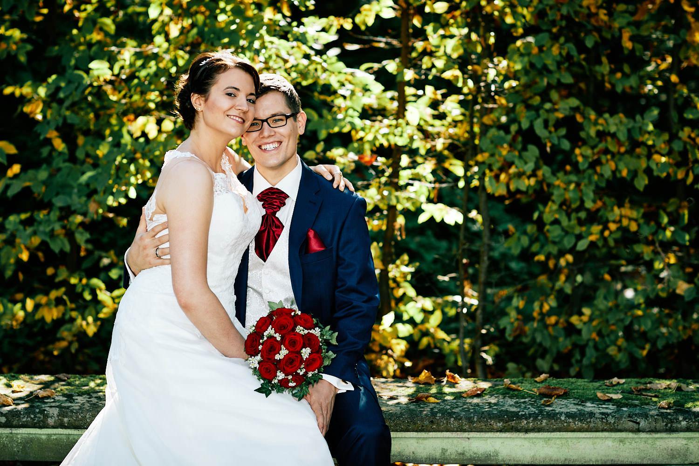 Hochzeitsfotograf in Schwetzingen - Jaqueline und Martin sitzen im Schwetzinger Schlossgarten beim Hochzeitsshooting auf einer Bank. Ein kleineres Bild.